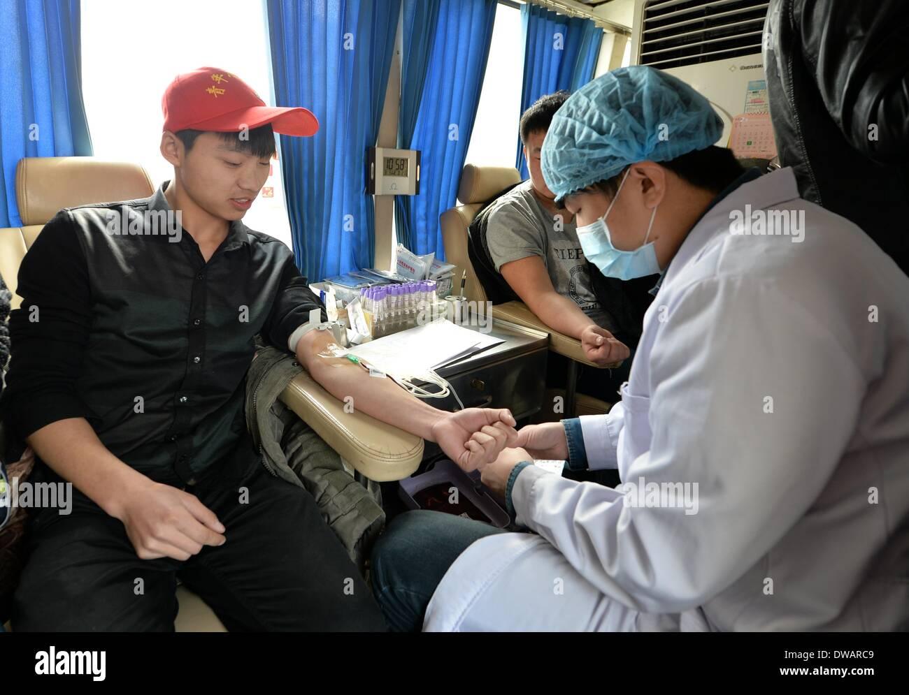 """Xingtai, soldato cinese negli anni sessanta. Il 15 agosto, 1962. Uno studente di college dona sangue nella città di Xingtai, nel nord della Cina di nella provincia di Hebei, 5 marzo 2014, in occasione della """"Lei Feng's Day"""", che cade il 5 marzo di ogni anno. Lei, un giovane soldato cinese negli anni sessanta, è noto per aver dedicato quasi tutto il suo tempo di ricambio e denaro per aiutare disinteressatamente i bisognosi. Egli è morto dopo essere stato colpito da una caduta di pole mentre aiutando un compagno soldato dirigere un carrello su 15 Agosto 1962. Credito: Zhu Xudong/Xinhua/Alamy Live News Immagini Stock"""