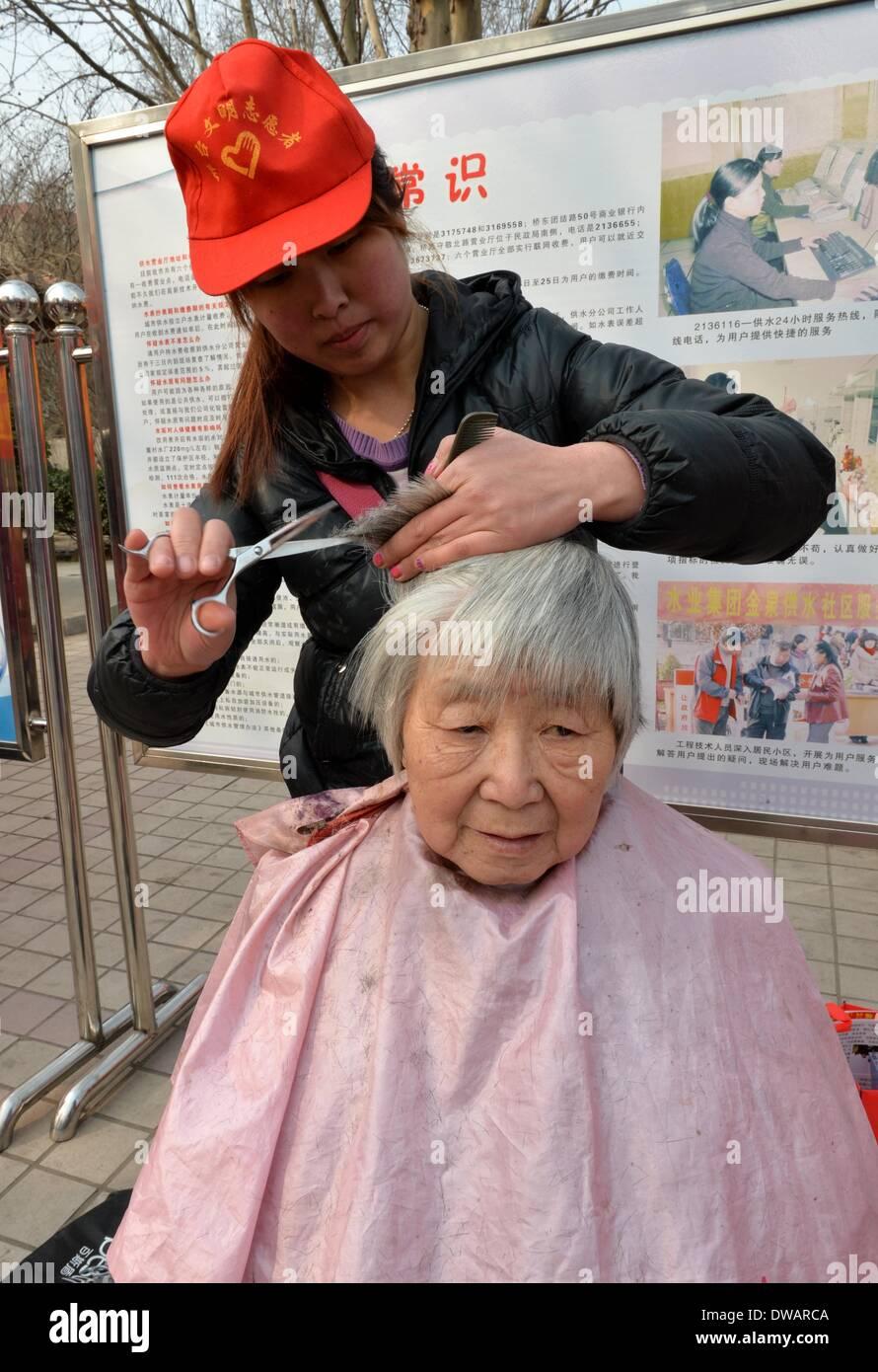"""Xingtai, soldato cinese negli anni sessanta. Il 15 agosto, 1962. Un volontario offre gratuitamente il servizio di acconciatura per una vecchia donna in Xingtai, città del nord della Cina nella provincia di Hebei, 5 marzo 2014, in occasione della """"Lei Feng's Day"""", che cade il 5 marzo di ogni anno. Lei, un giovane soldato cinese negli anni sessanta, è noto per aver dedicato quasi tutto il suo tempo di ricambio e denaro per aiutare disinteressatamente i bisognosi. Egli è morto dopo essere stato colpito da una caduta di pole mentre aiutando un compagno soldato dirigere un carrello su 15 Agosto 1962. Credito: Zhu Xudong/Xinhua/Alamy Live News Immagini Stock"""