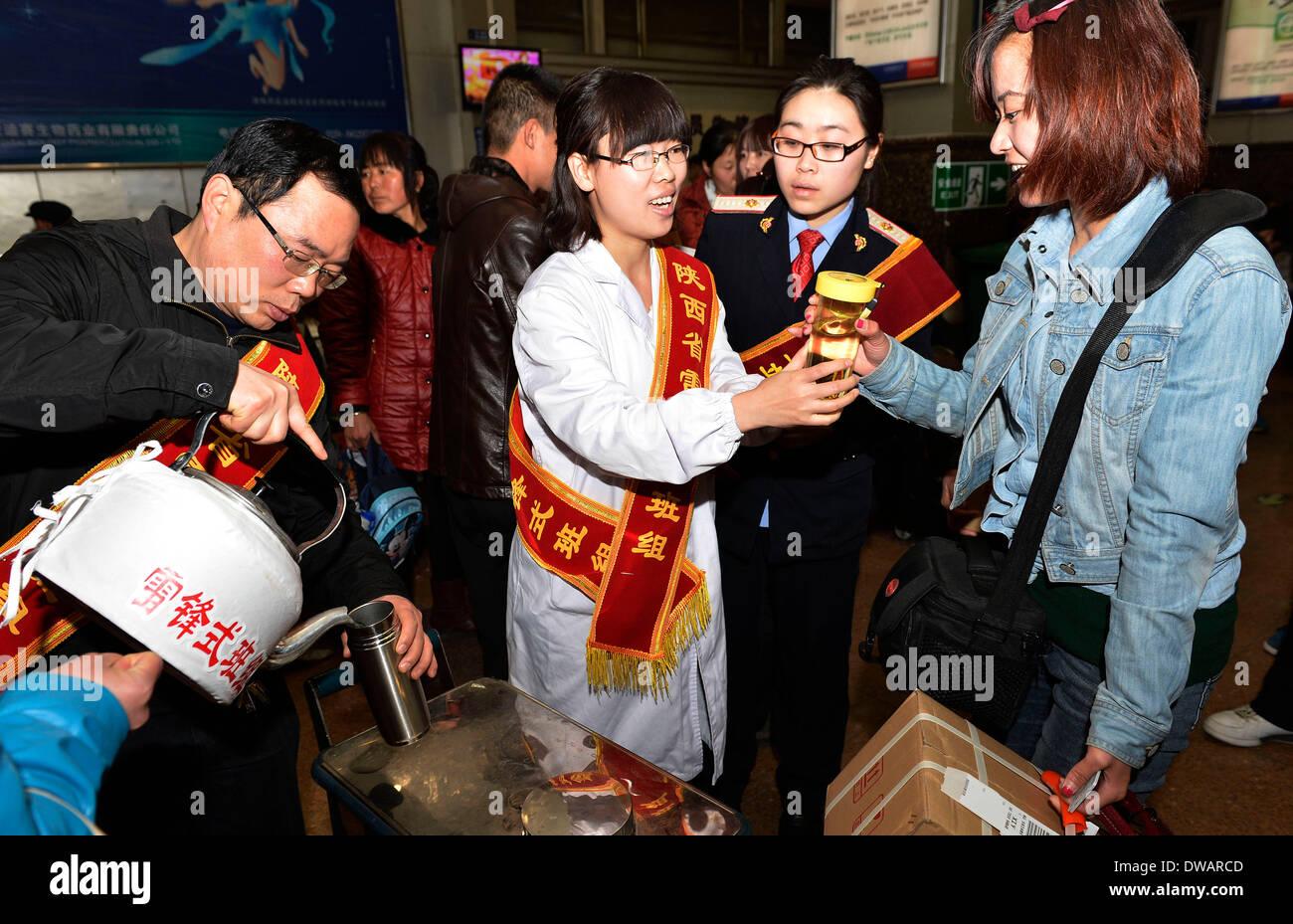 """Xi'an, soldato cinese negli anni sessanta. Il 15 agosto, 1962. Volontari erogare acqua per i passeggeri a Xi'an Stazione Ferroviaria di Xi'an, capitale della Cina nord-occidentale della provincia di Shaanxi, 5 marzo 2014, in occasione della """"Lei Feng's Day"""", che cade il 5 marzo di ogni anno. Lei, un giovane soldato cinese negli anni sessanta, è noto per aver dedicato quasi tutto il suo tempo di ricambio e denaro per aiutare disinteressatamente i bisognosi. Egli è morto dopo essere stato colpito da una caduta di pole mentre aiutando un compagno soldato dirigere un carrello su 15 Agosto 1962. Credito: Liu Xiao/Xinhua/Alamy Live News Immagini Stock"""