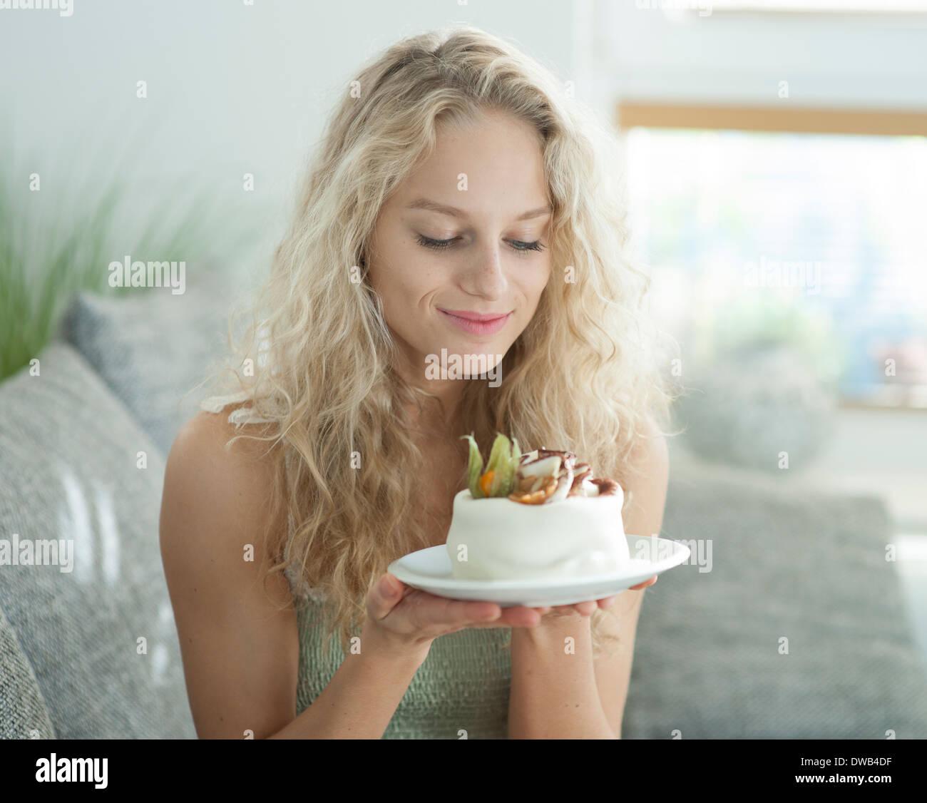 Giovane e bella donna che guarda la torta allettante in casa Immagini Stock