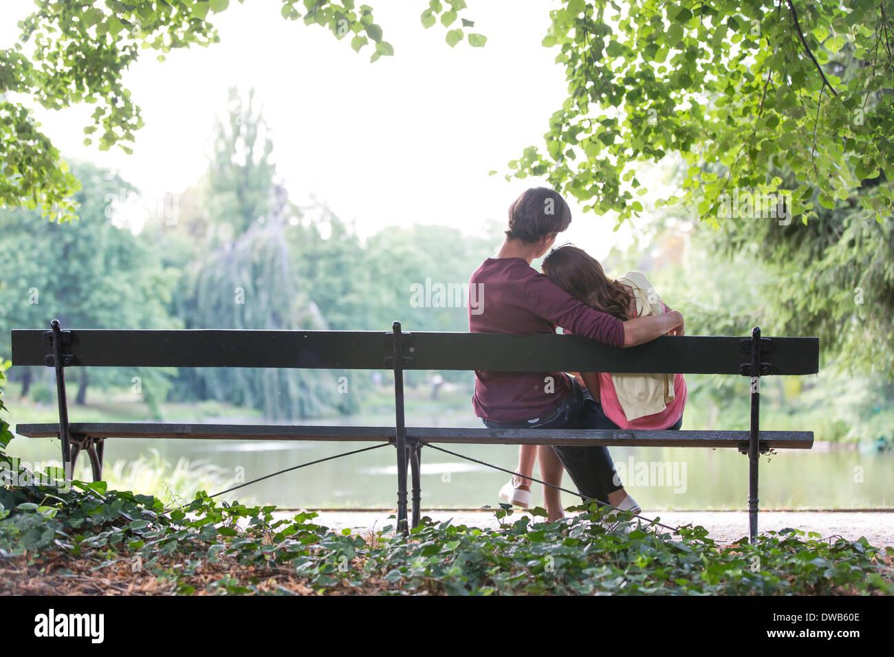 Vista posteriore della romantica coppia giovane seduto sul banco a Lakeside Immagini Stock
