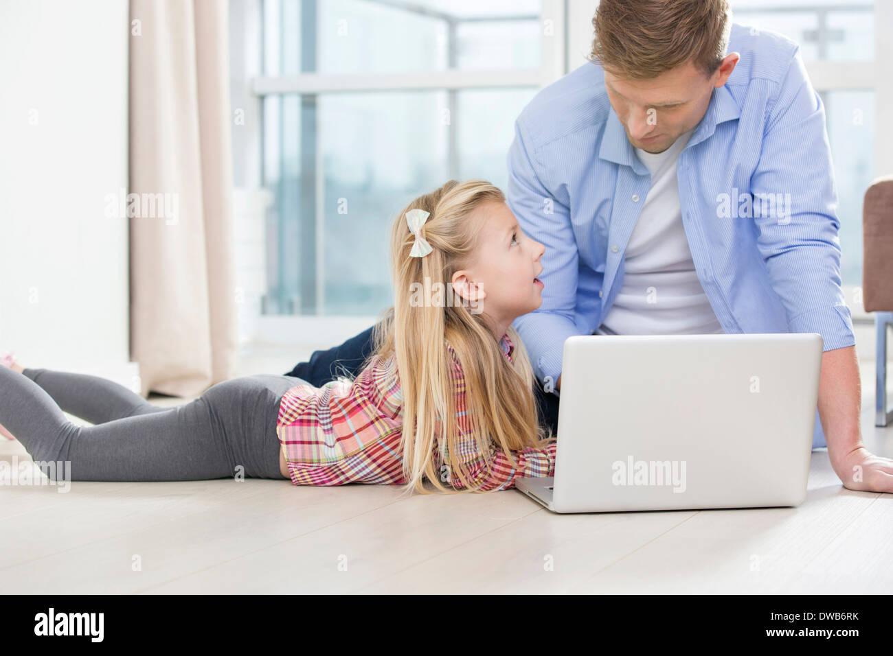 Padre e figlia utilizzando laptop sul pavimento nel soggiorno Immagini Stock
