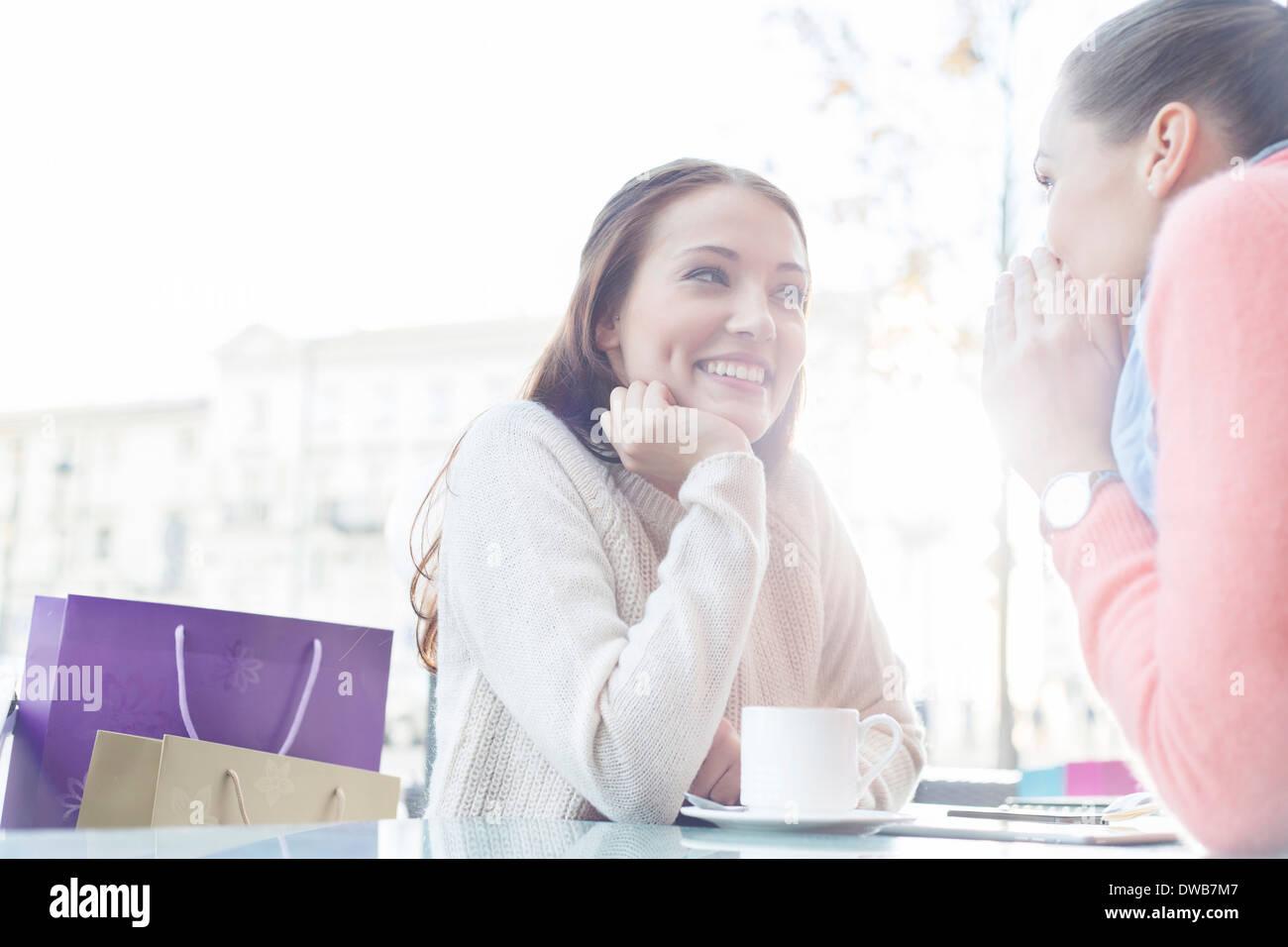 Bella giovane donna guardando amico segreti di condivisione in outdoor cafe Immagini Stock