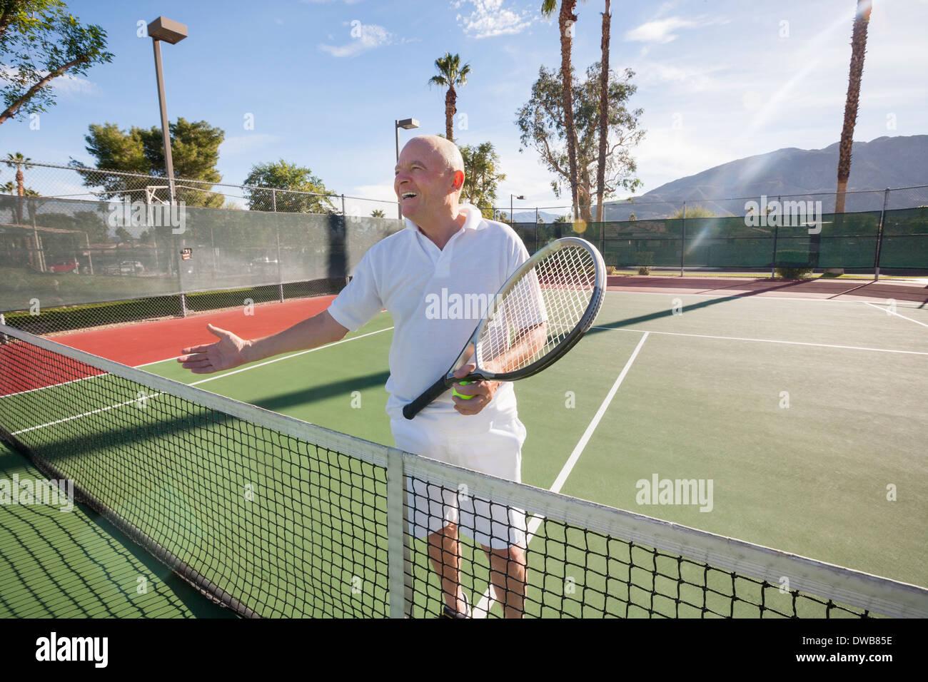 Felice senior tennista offrendo handshake su corte Immagini Stock