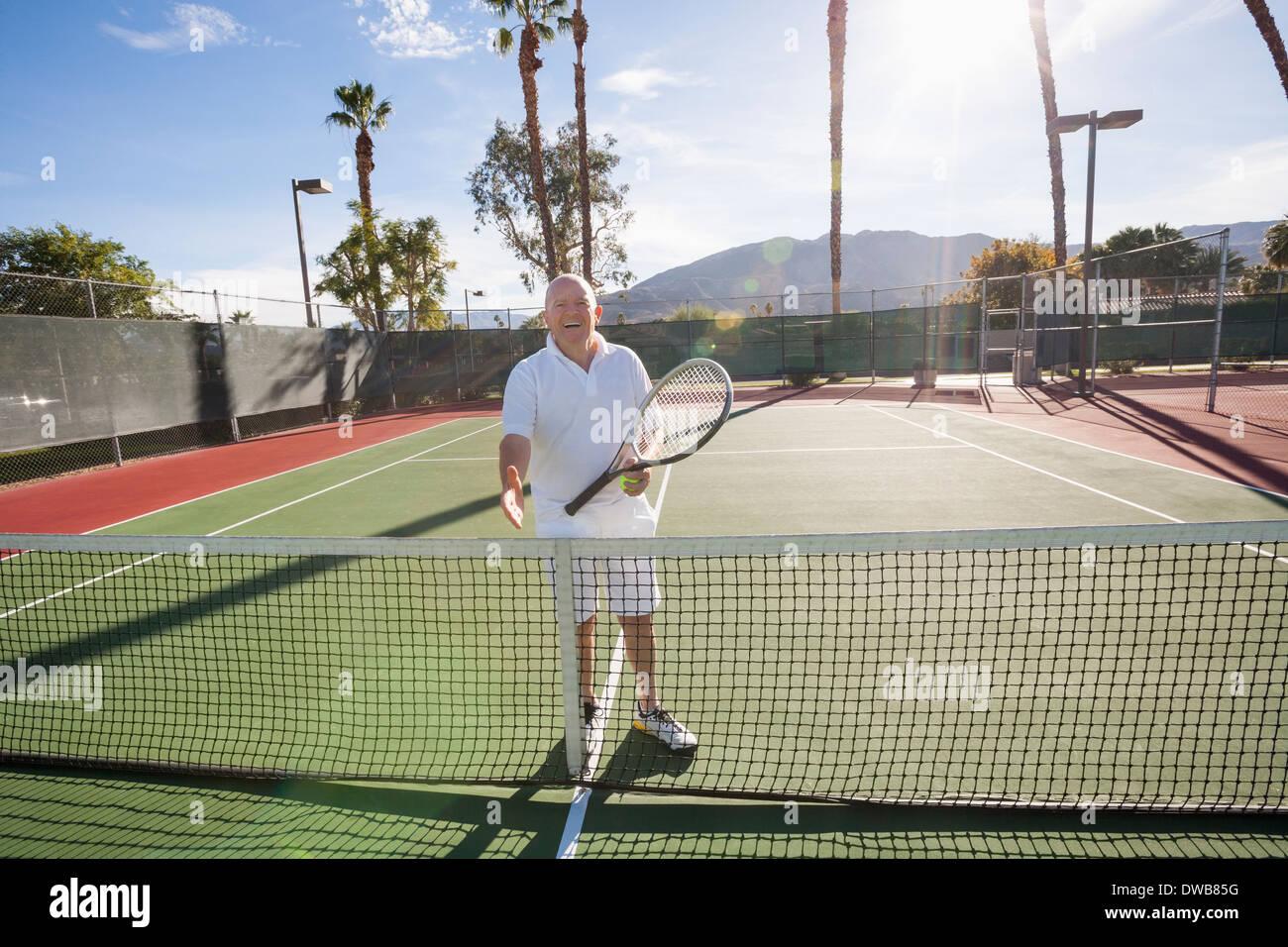 Ritratto di senior giocatore di tennis offrendo handshake su corte Immagini Stock