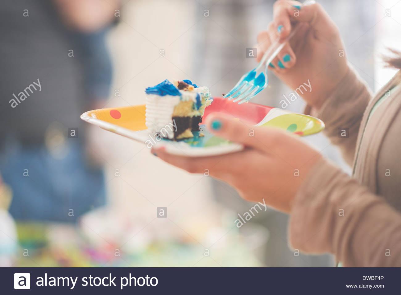 Close up della ragazza adolescente mangiare fetta di torta di compleanno Immagini Stock