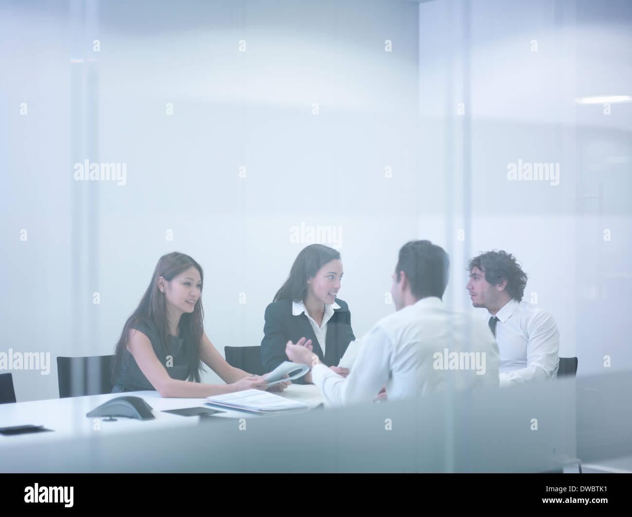 Vista attraverso la parete di vetro di colleghi di lavoro di riunione Immagini Stock