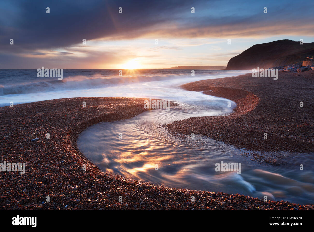 Winniford sul fiume che scorre verso il mare a Seatown spiaggia con scogliere di Golden Cap in distanza. Jurassic Foto Stock