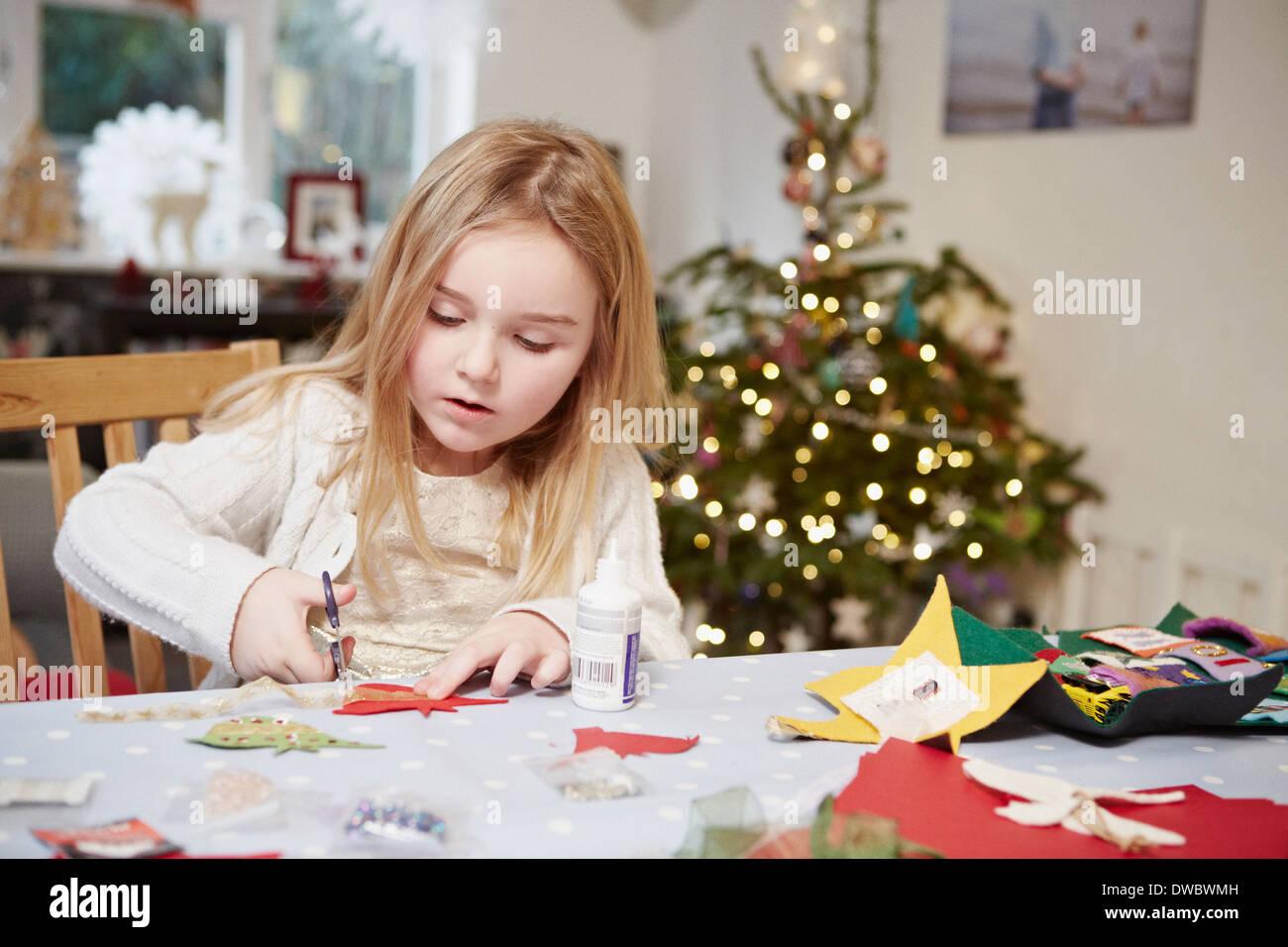 Giovane ragazza il taglio del documento in preparazione al Natale Immagini Stock