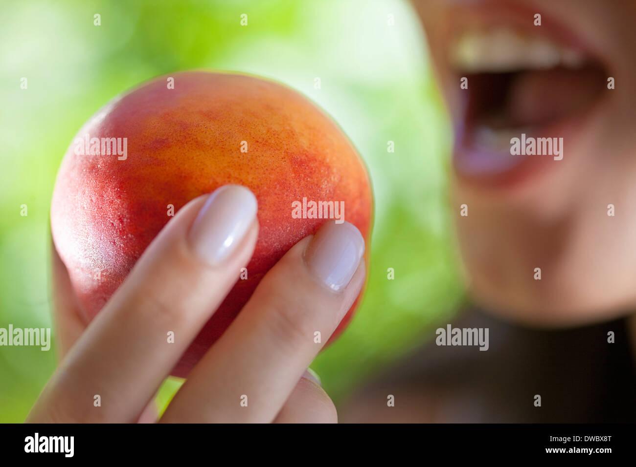 Donna che mantiene peach a bocca Immagini Stock