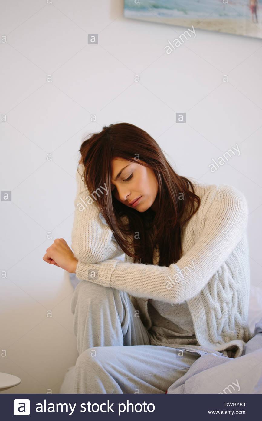 Giovane donna seduta a letto Immagini Stock