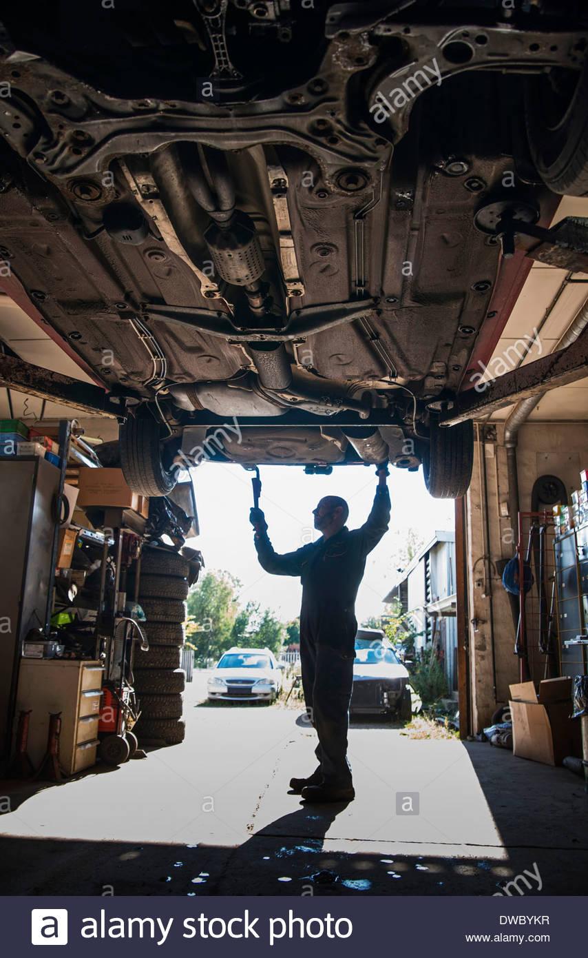 Lunghezza completa di meccanico che lavora nel negozio di riparazioni auto Immagini Stock