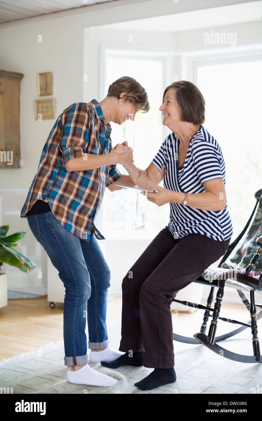Donna matura aiutando la madre di alzarsi dalla sedia a casa Immagini Stock