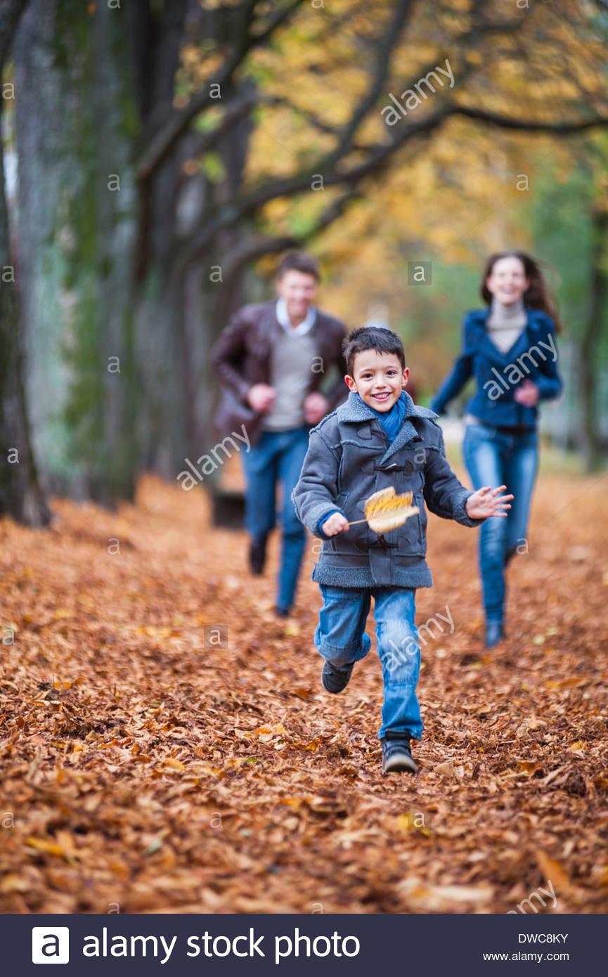 Ragazzo giovane e genitori che corre attraverso le foglie di autunno nel parco Immagini Stock