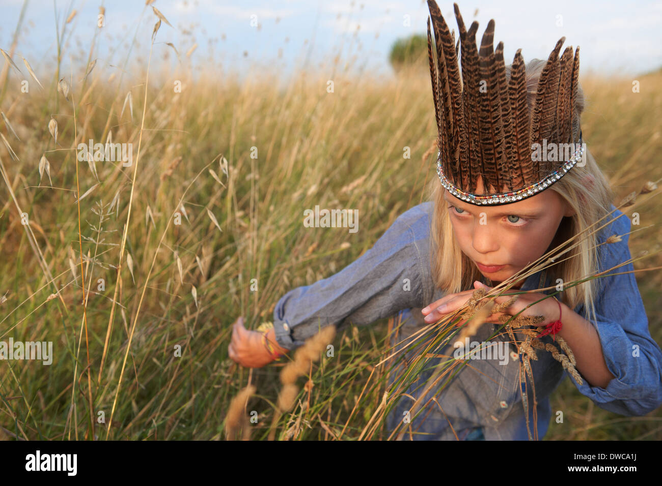 La ragazza si nasconde in erba lunga vestito come un nativo americano Immagini Stock
