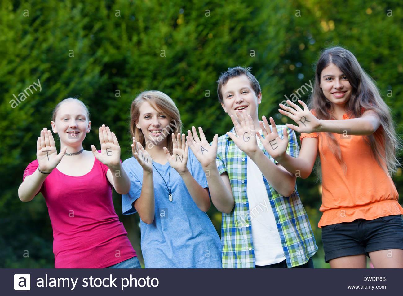 Tre ragazze e un ragazzo che mostra insieme la parola adolescente sui loro palmi Immagini Stock