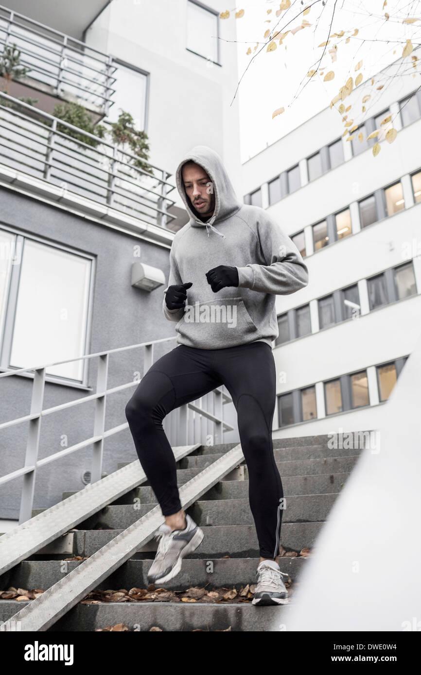 Uomo sportivo si sta spostando verso il basso le scale Immagini Stock
