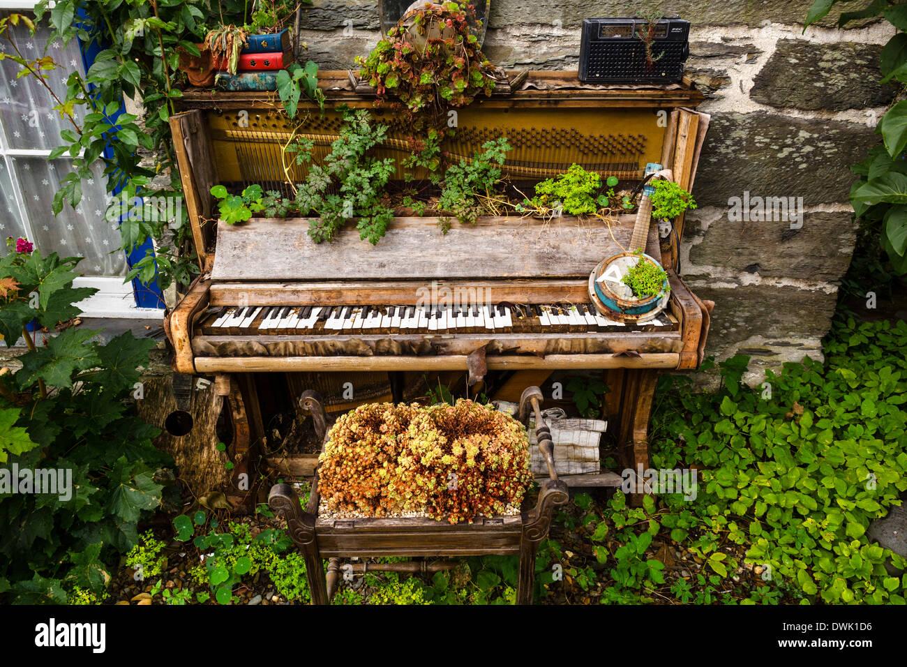 Vecchio pianoforte e pianoforte sgabello usato come fioriere nel