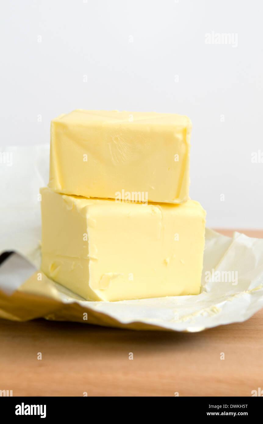 Aprire il pacco di burro sul tagliere di legno Immagini Stock
