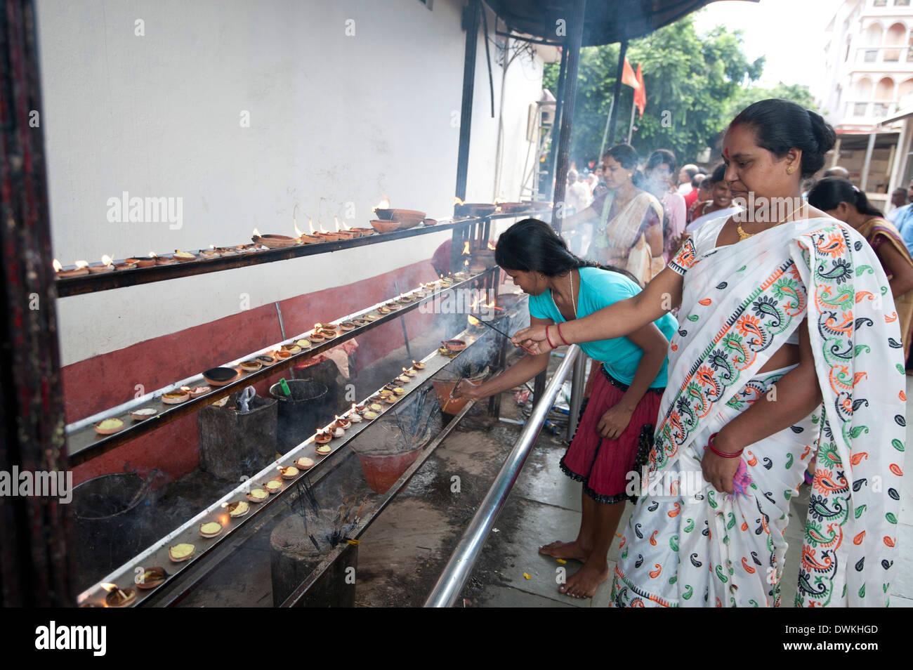Donna indù in bianco sari eseguendo puja mediante illuminazione diya (candela) nel tempio Kamakhya, Guwahati, Assam, India, Asia Immagini Stock