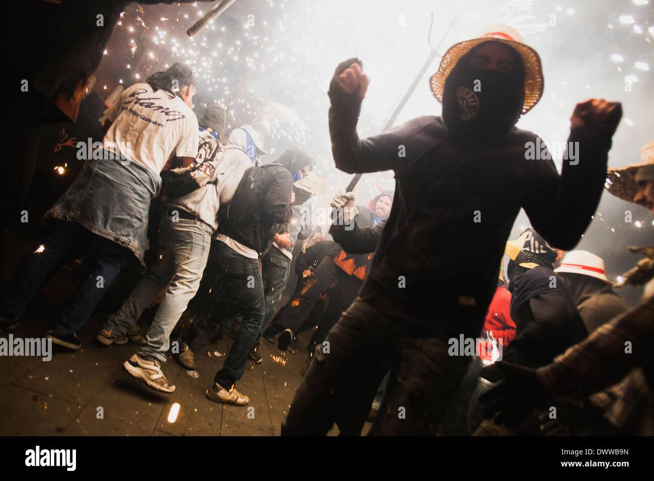 La gente ballare sotto i fuochi d'artificio di un correfoc, una tradizione catalana Immagini Stock