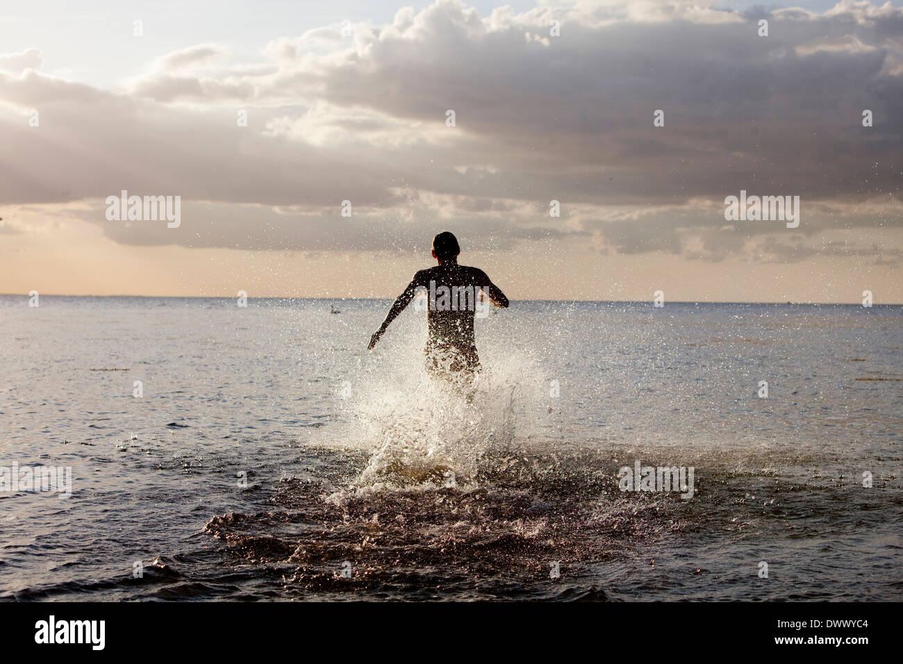 Vista posteriore dell'uomo in esecuzione in mare Immagini Stock