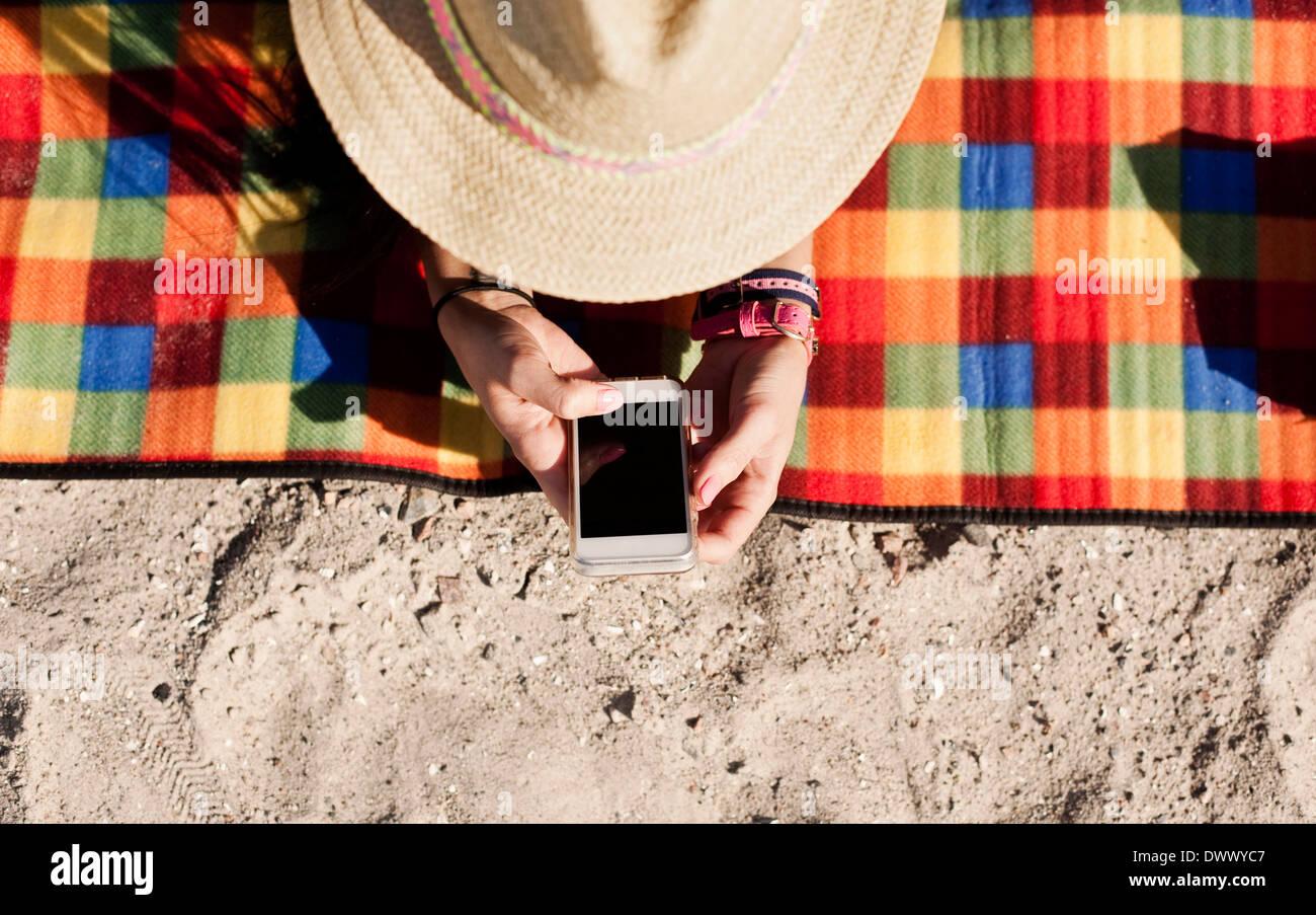 Elevato angolo di visione della donna che utilizza il cellulare mentre giacente sulla coperta picnic Immagini Stock