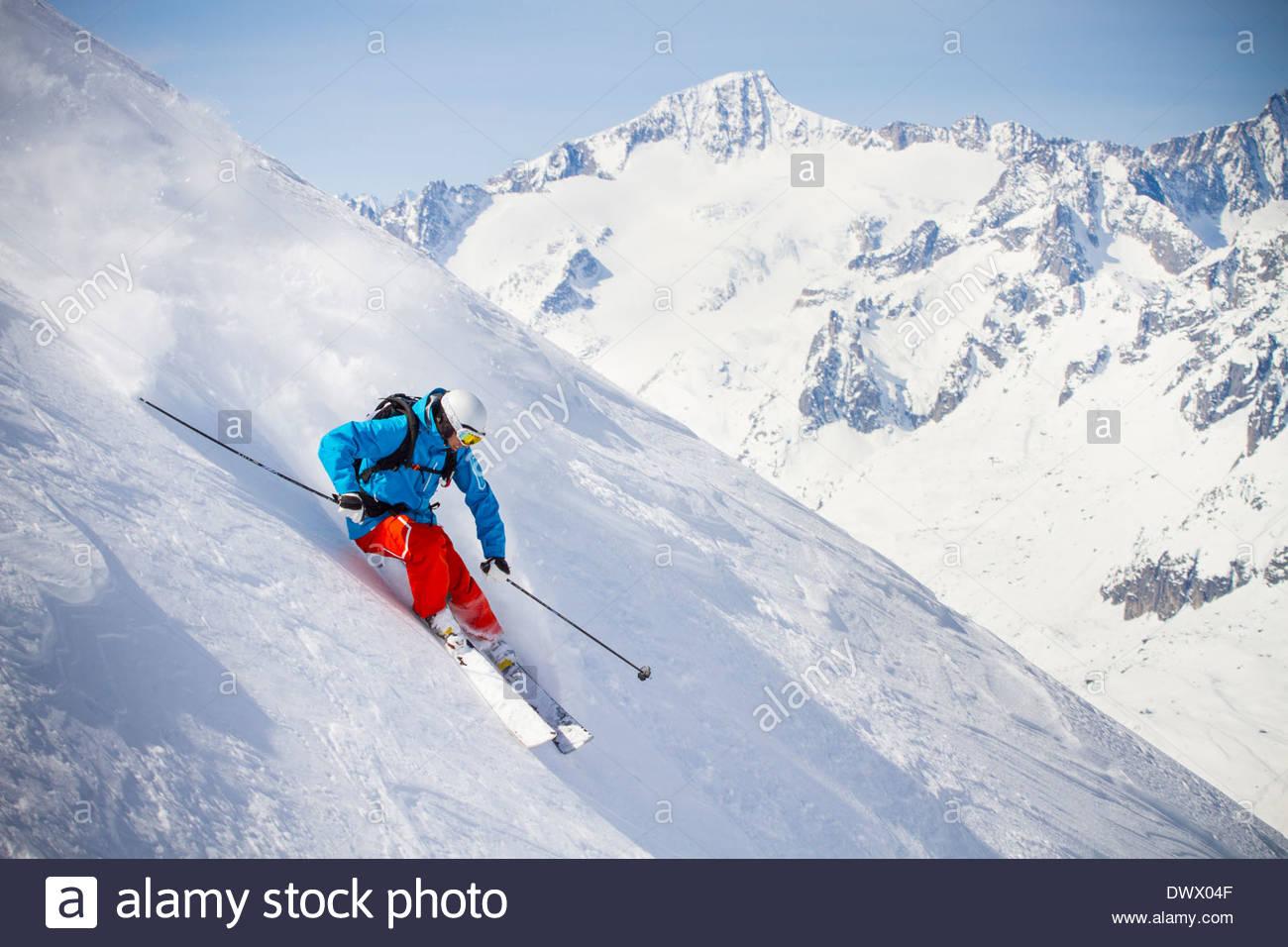 Lunghezza completa dell'uomo sciare sul pendio di montagna Immagini Stock
