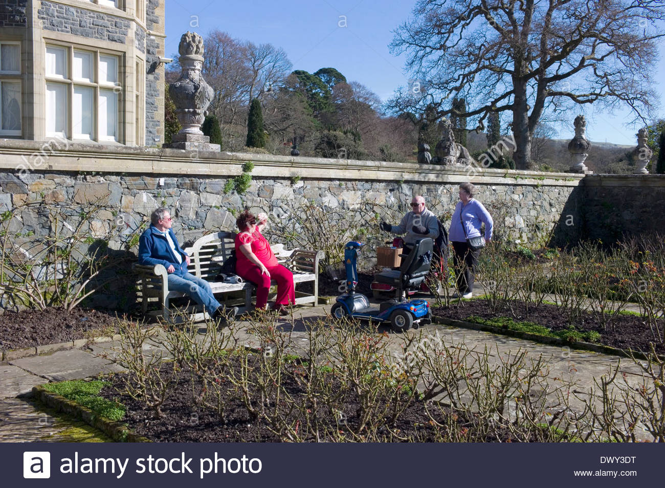 Due coppie mature con la loro disabilità scooter in appoggio su una panchina Lutyens a Bodnant Gardens, Conwy Valley, il Galles del Nord Immagini Stock