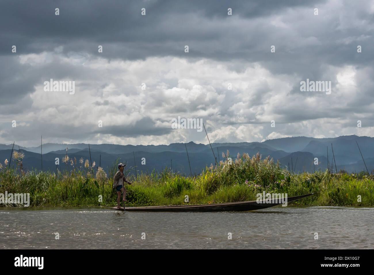 Gamba vogatore in mano cr piroga dalla riva del lago con storm brewing, Lago Inle, Myanmar Immagini Stock