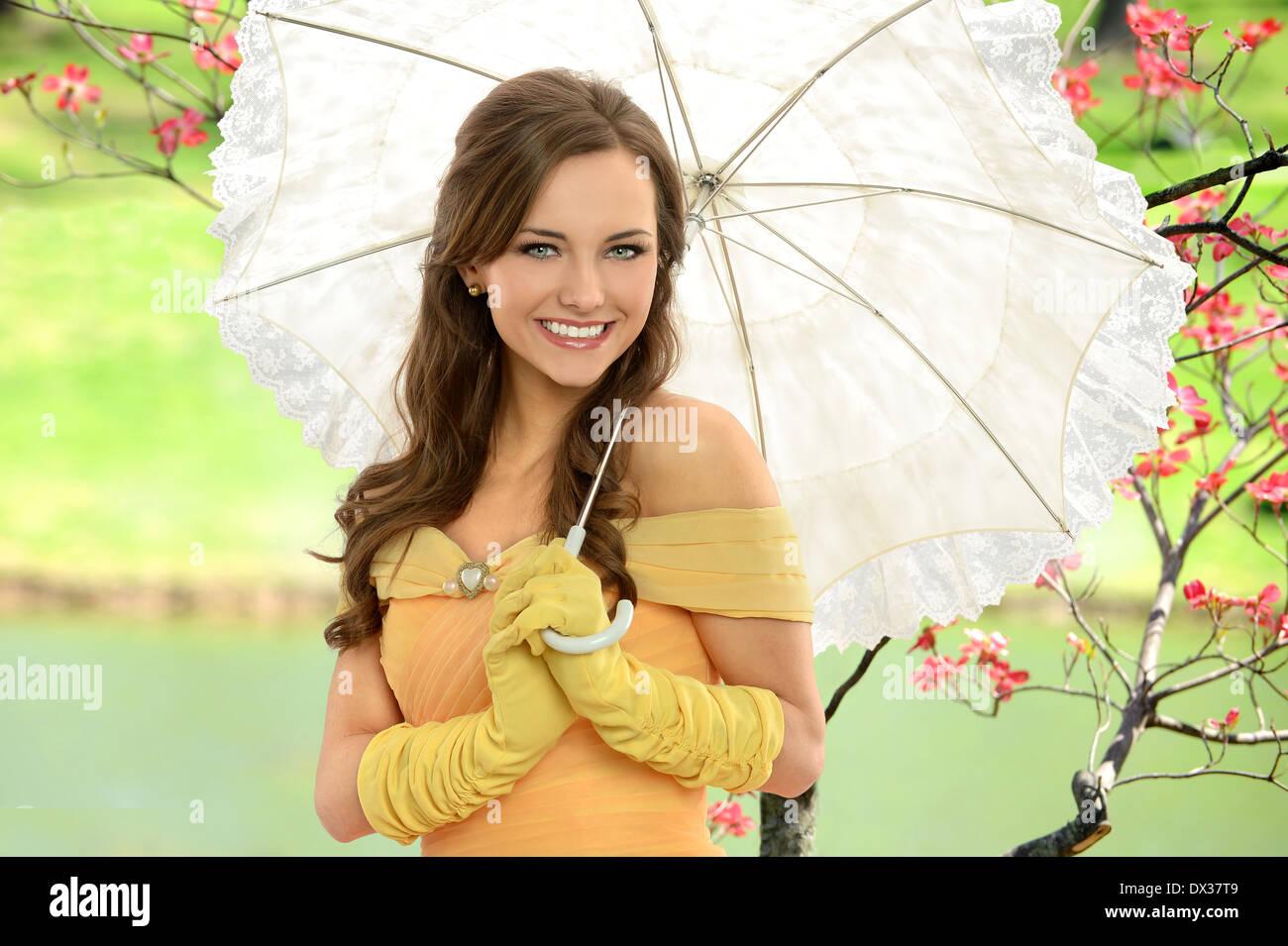 Ritratto di giovane donna in abito vittoriano holding ombrello all'aperto Foto Stock