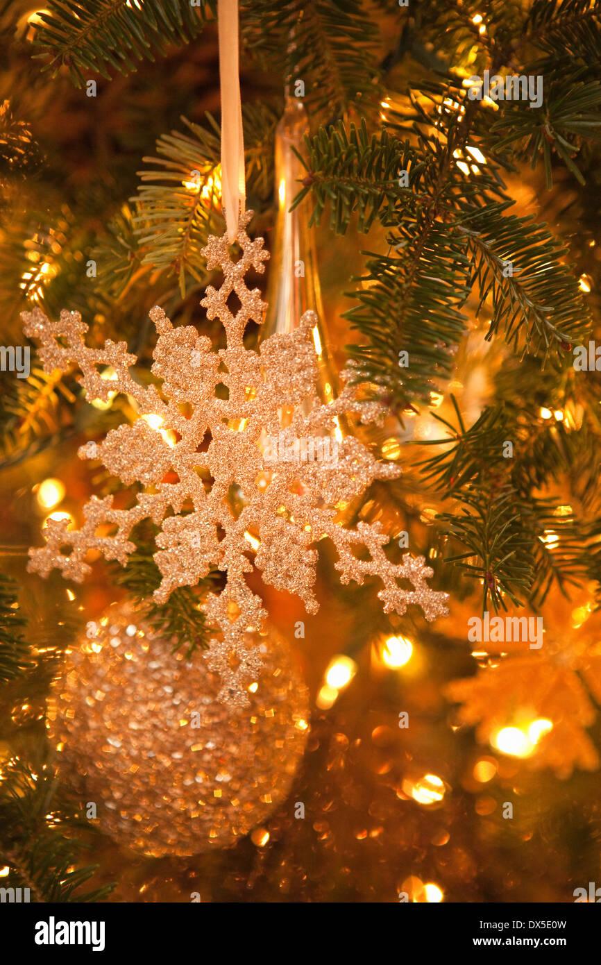 Il simbolo del fiocco di neve scintillanti e la sfera di ornamenti appesi in accesa albero di Natale Immagini Stock