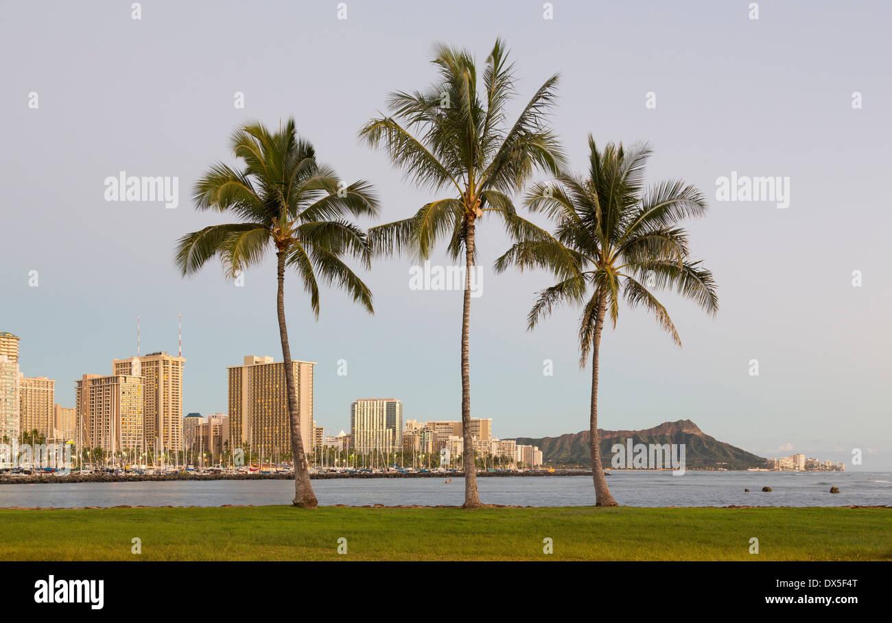 Di Honolulu e Waikiki da Ala Moana Park come il sole tramonta con tre alberi di palma, Hawaii, STATI UNITI D'AMERICA Immagini Stock