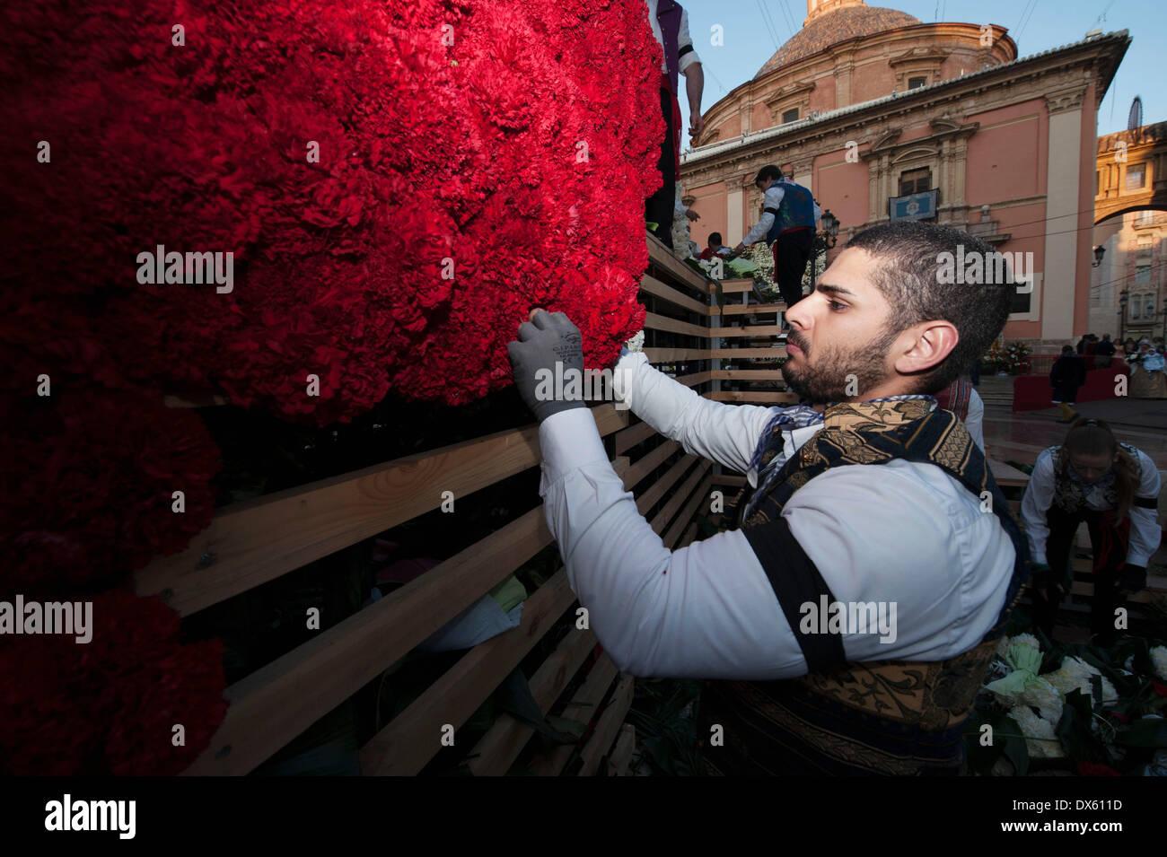 Valencia, Spagna. Xviii Mar, 2014. Un uomo decora la gigantesca scultura della Vergine con fiori durante il Fallas Foto Stock