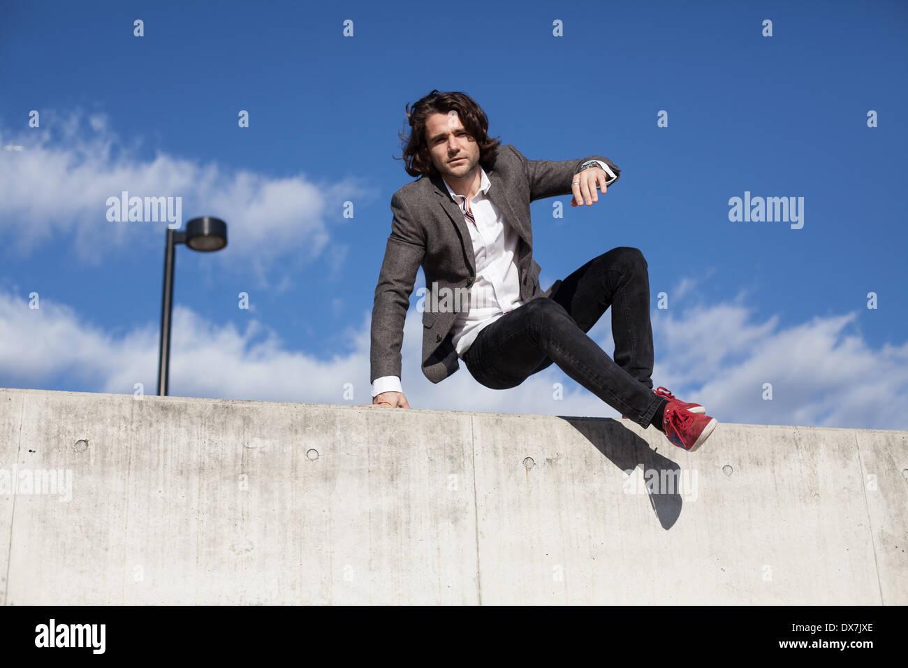 Un giovane maschio modello su un muro di cemento con cielo blu dietro Immagini Stock