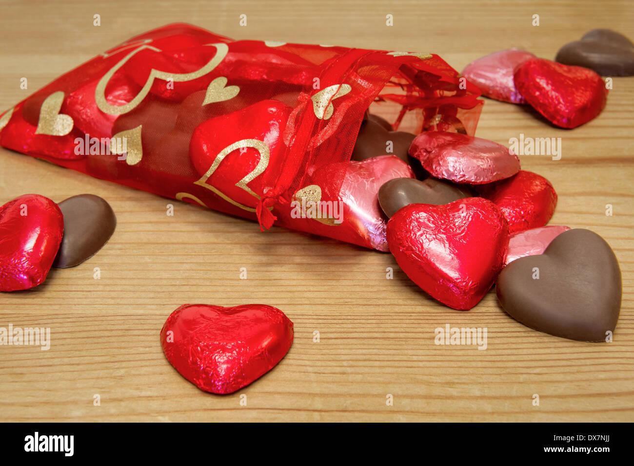 Un sacchetto rosso pieno di a forma di cuore sweetheart cioccolatini riversandosi su di un tavolo di legno. Immagini Stock