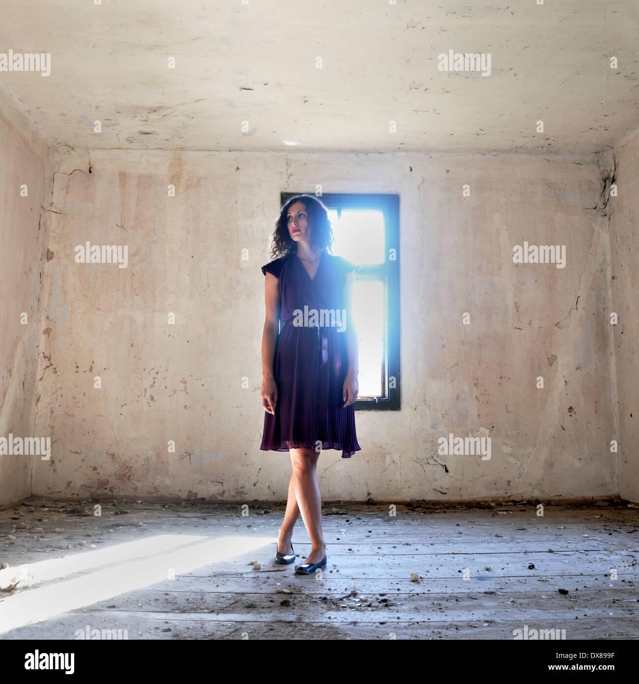 Donna in piedi dalla finestra Foto Stock