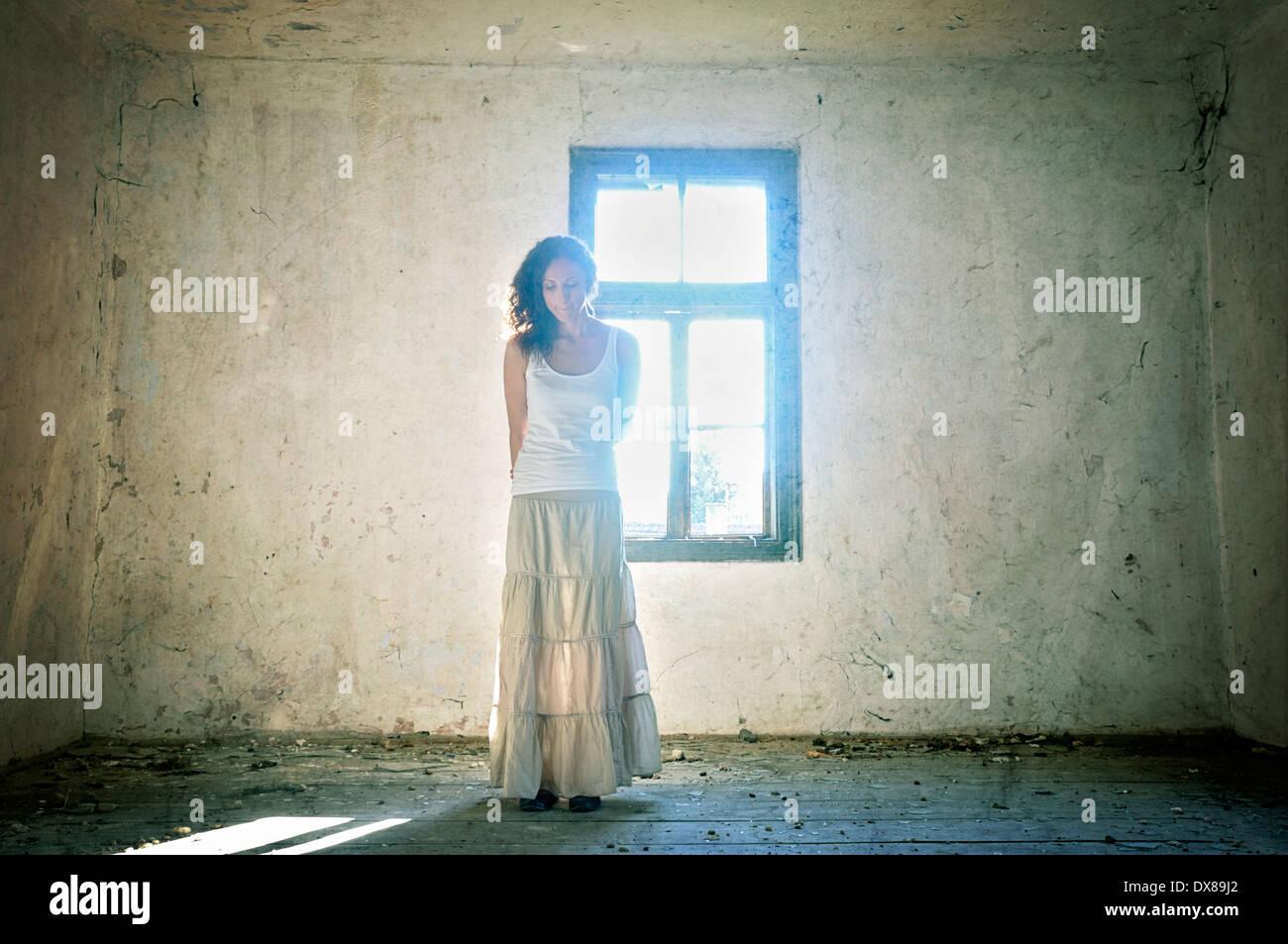 Donna in piedi dalla finestra Immagini Stock