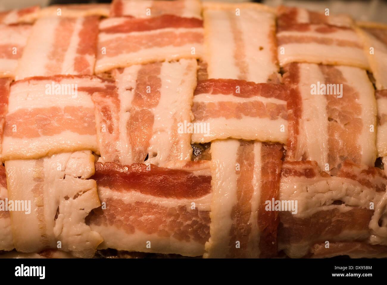 Polpettone crudo avvolto con il bacon in una cesta modello di armatura seduto in un chiaro in Pyrex teglia su una cucina piano cottura Immagini Stock
