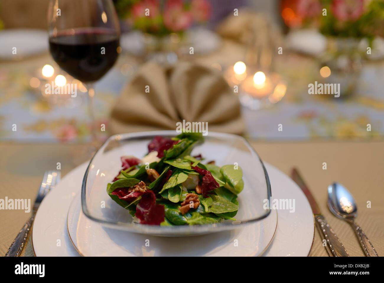 Primo corso insalata in home sala da pranzo tavolo per una cena con il tovagliolo e vino rosso Immagini Stock