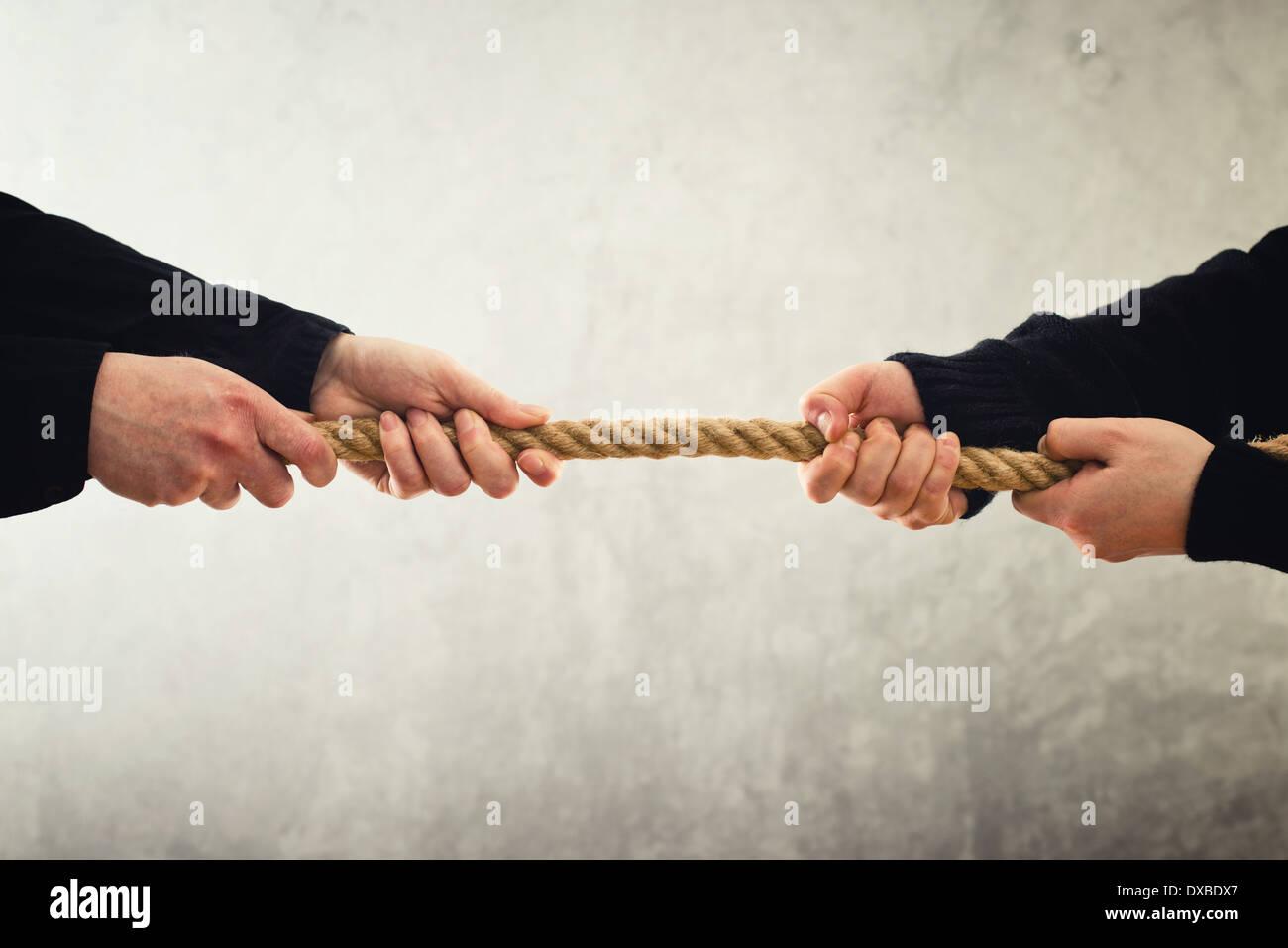 Rimorchiatore di guerra. Mani femminili tirando la corda di lati opposti. Concetto di rivalità. Immagini Stock