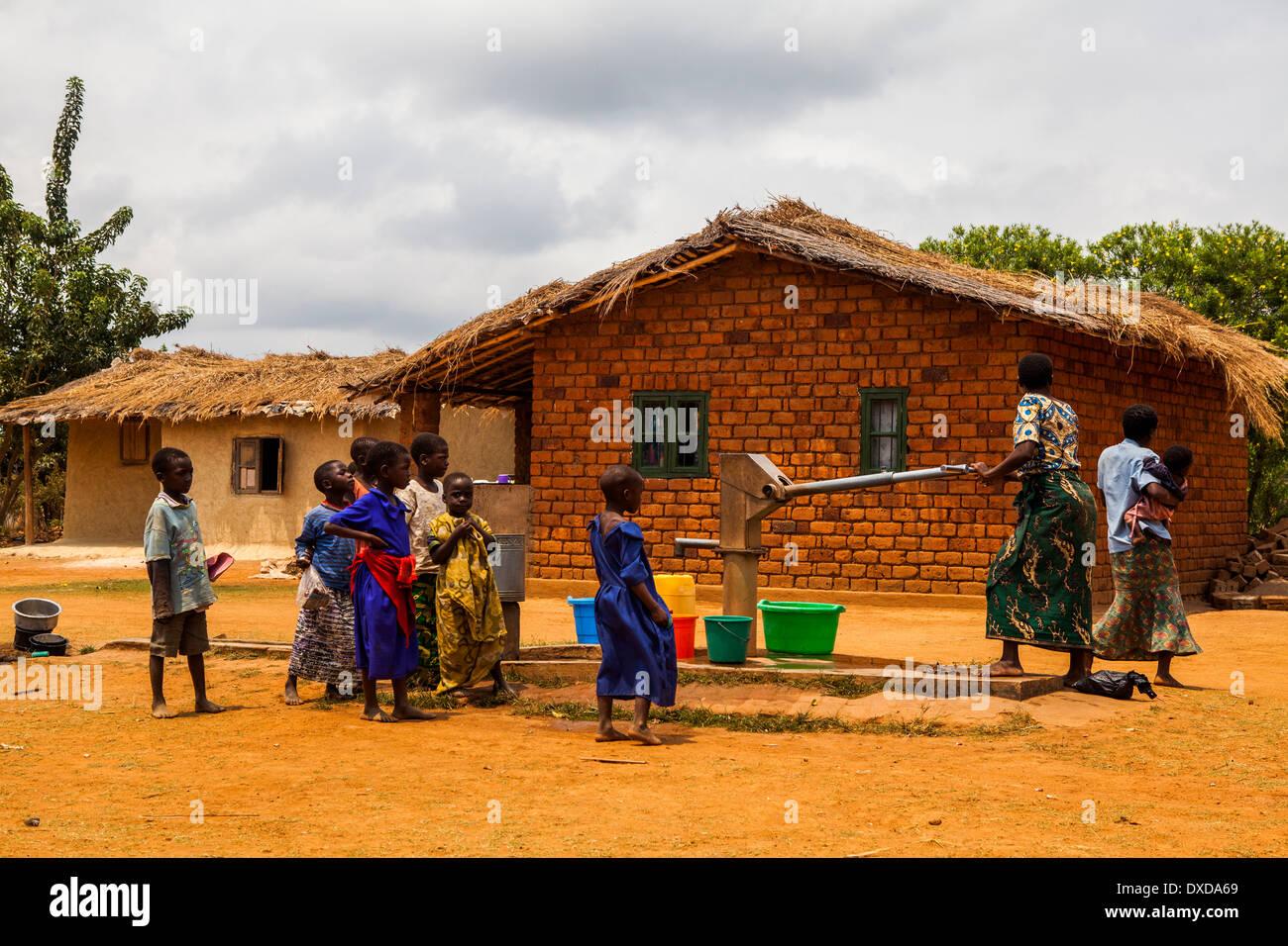 Gli abitanti di un villaggio africano di raccogliere acqua ad una comune pompa acqua Immagini Stock
