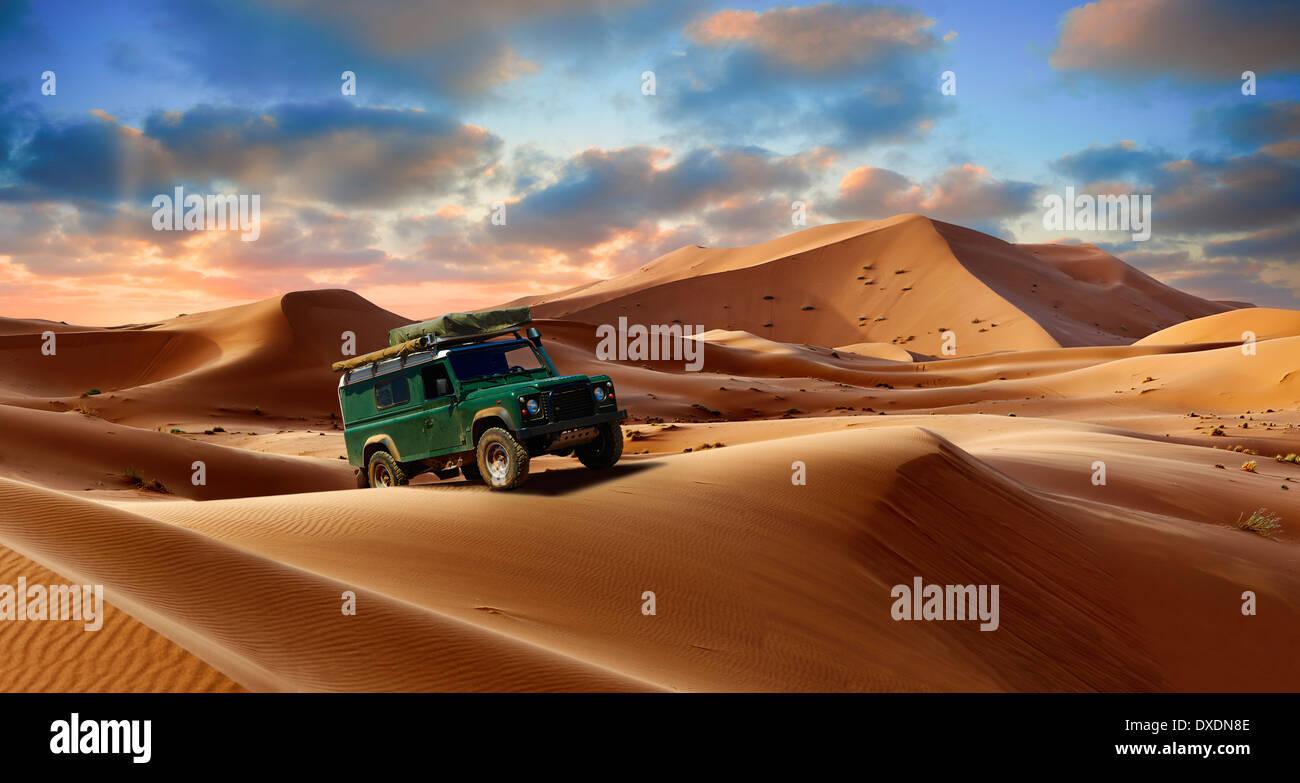 4 x4 Land Rover Defender sul Sahara dune di sabbia di Erg Chebbi al tramonto , Marocco, Africa Foto Stock