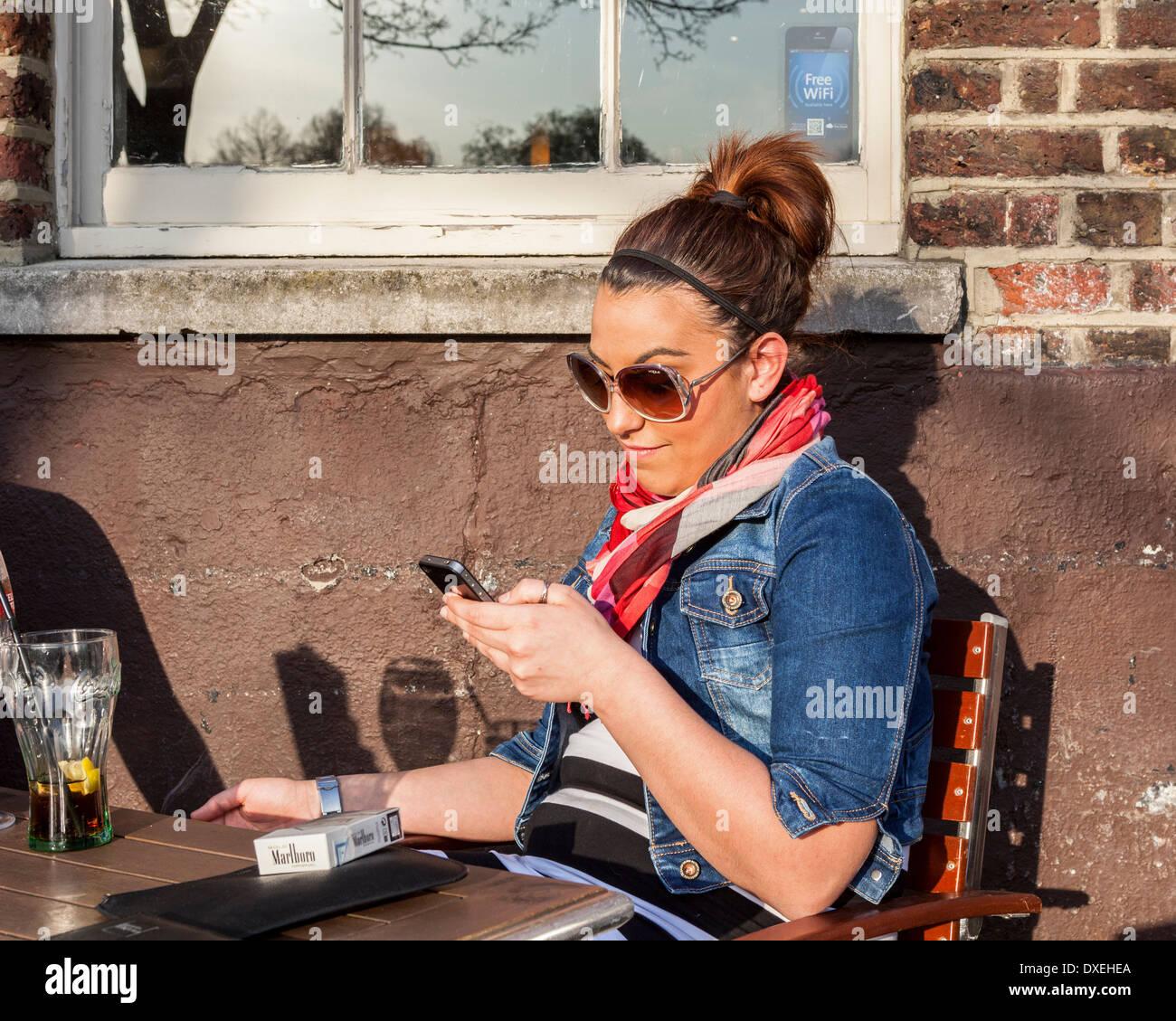 Attraente giovane donna di relax all'aperto e utilizzando i-phone Immagini Stock