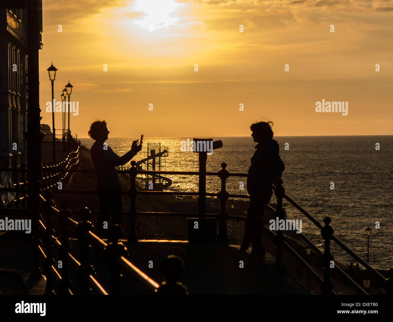 Persona che ha preso una foto del telefono cellulare sul lungomare a Cromer come il sole tramonta Inghilterra Immagini Stock