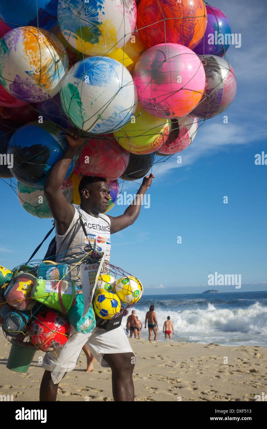 RIO DE JANEIRO, Brasile - 19 gennaio 2014: Spiaggia venditore a vendere pittoresca spiaggia di sfere porta la sua merce lungo la spiaggia di Ipanema Immagini Stock