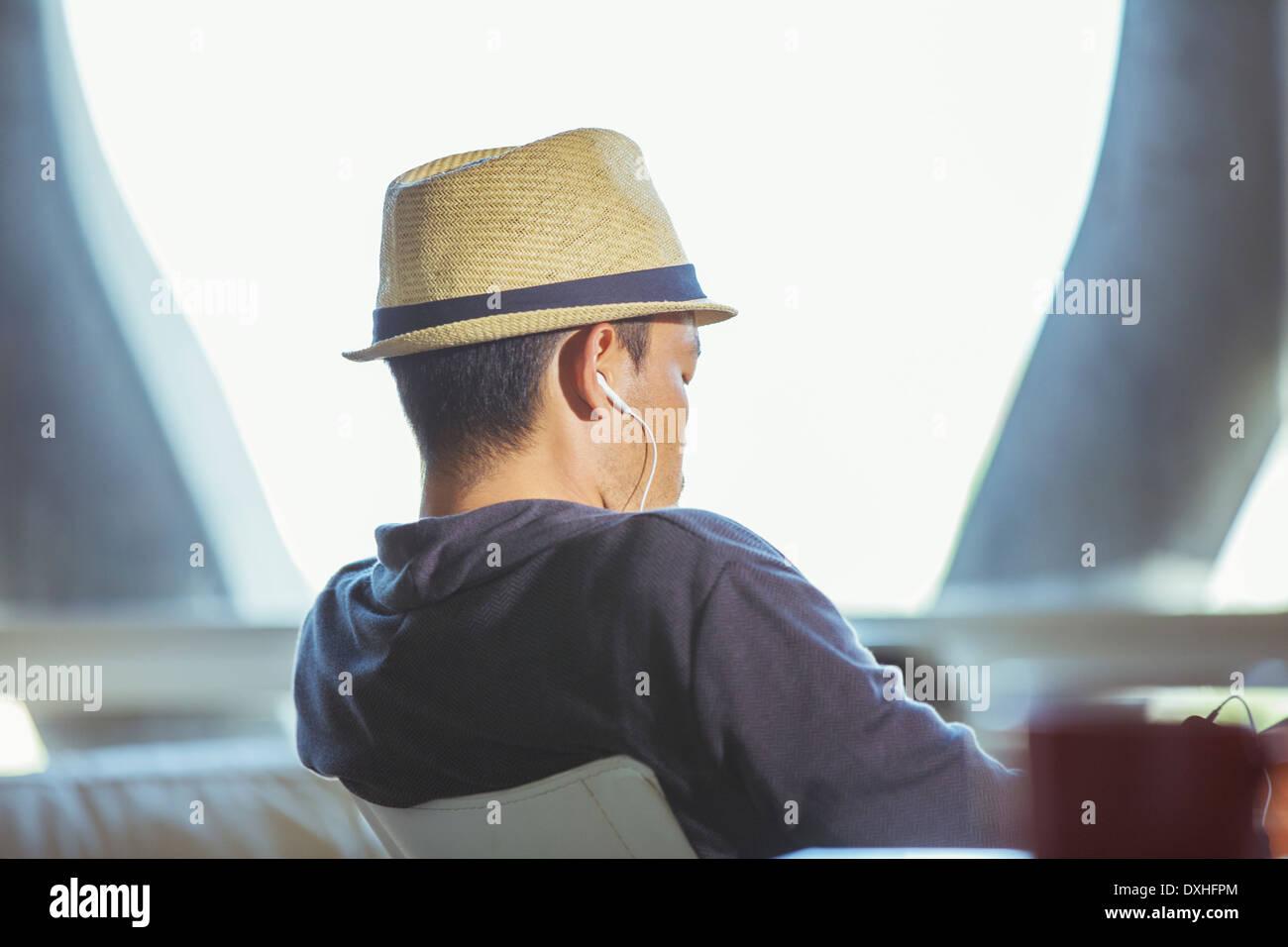 Uomo in fedora che indossano le cuffie Foto Stock