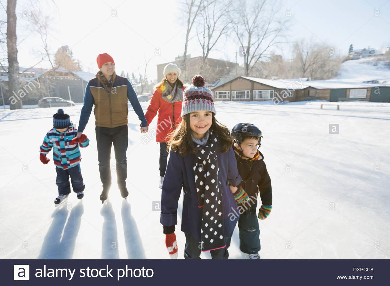 Famiglia pattinaggio sul ghiaccio all'aperto insieme Immagini Stock