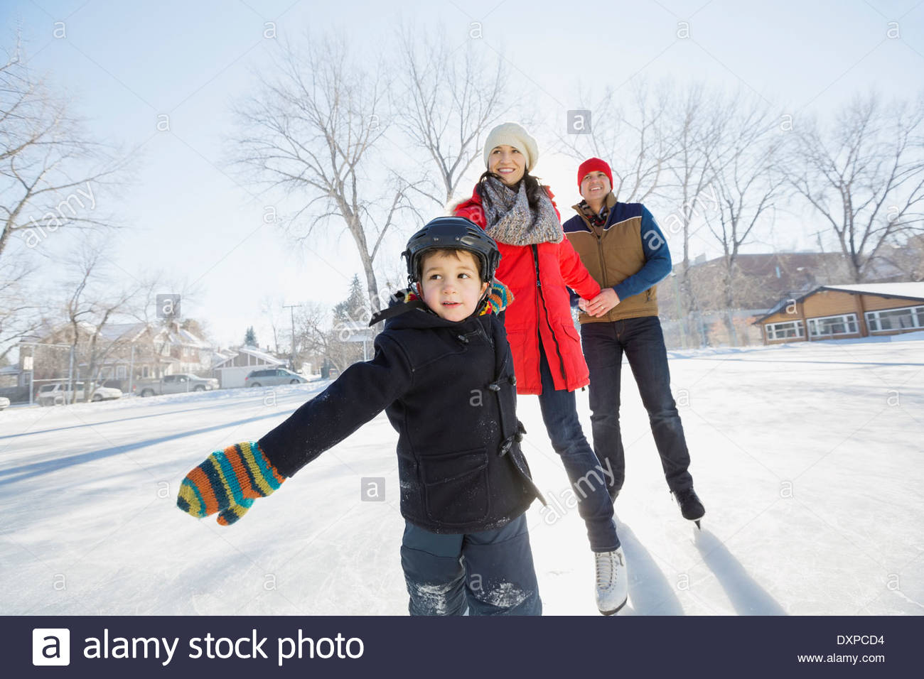 Ragazzo del pattinaggio su ghiaccio con i genitori sulla pista di pattinaggio all'aperto Immagini Stock