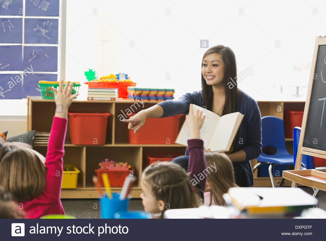 Insegnante rivolti a studenti con le mani alzate nella classe Immagini Stock
